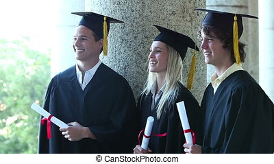 Trhee graduates laughing together while standing outsides