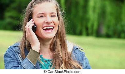 Joyful woman using a cellphone in a park