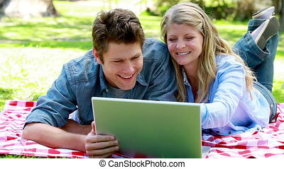 Couple using a laptop on the floor in a park
