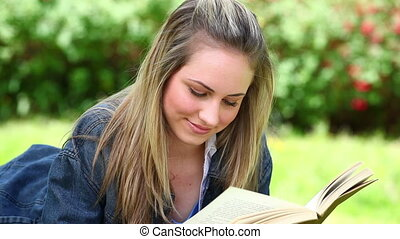 Happy blonde woman reading a book in a park