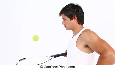 Tennis man bouncing ball on racket against white background
