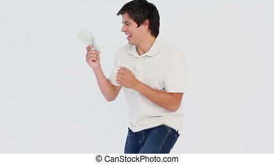 Man holding money against plain background