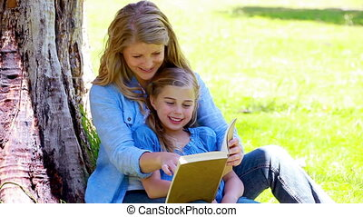 Woman reading a book with her daughter