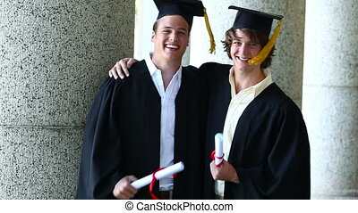 Smiling boys holding their diplomas