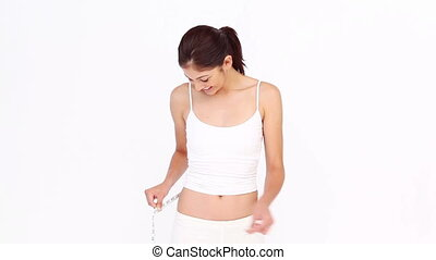 Brunette measuring her waist against white background