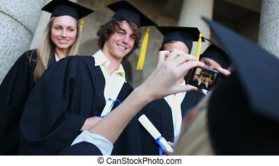 Smiling graduated students being photographed in front of...