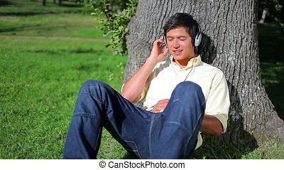 Peaceful man leaning against a tree while listening to music