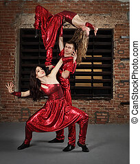 Dancers in action against brick wall
