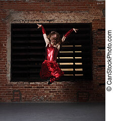 Young smiling blonde girl dancing over brick wall