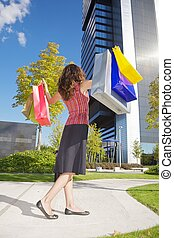 happy shopper woman down skyscrapers - brunette woman with...