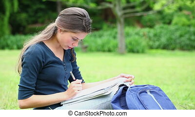 Cheerful student doing her homework in a park