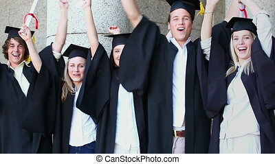 Smiling classmates raising their diplomas in front of the...