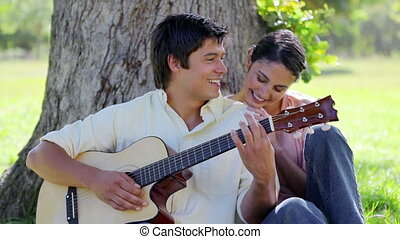Happy woman listening to her boyfriend playing a guitar in...