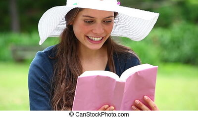 Smiling woman holding a book in a park