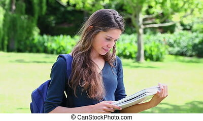Happy young woman studying in the countryside