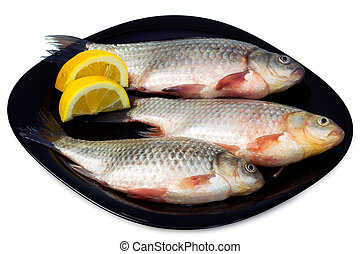 Fresh fish - bream with lemon wedges on a black plate,...