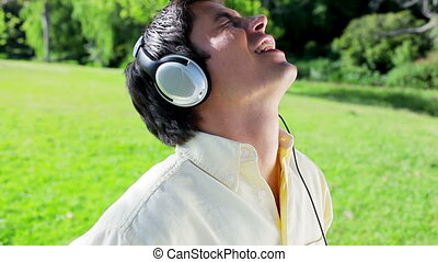Happy man listening to music while singing in a parkland