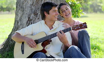 Laughing man playing a guitar for his girlfriend in the...