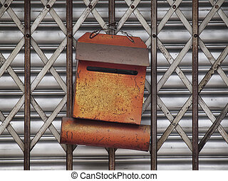 Letter box - Rusty orange letter box on a metallic gate