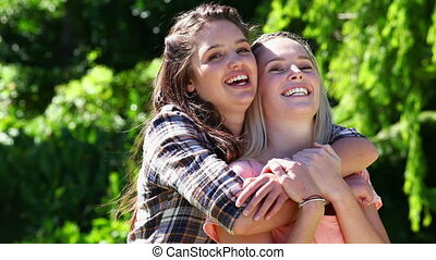 Happy woman placing her arms around her friend