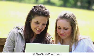 Happy friends using a laptop