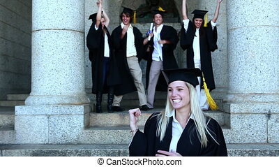 Graduates celebrating their graduation - Graduates...