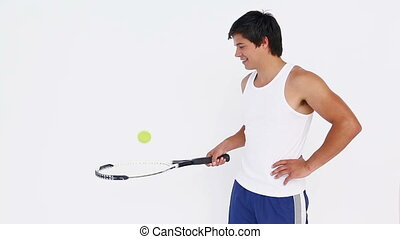 Tennis player bouncing ball on racket
