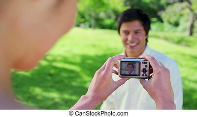 Happy woman taking her boyfriends picture in the countryside
