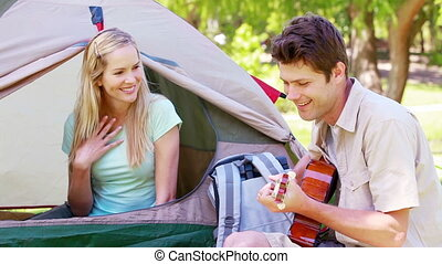 Man singing a song to his girlfriend while camping
