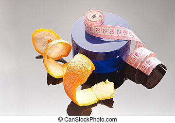 Cream can and orange peel on glassy background