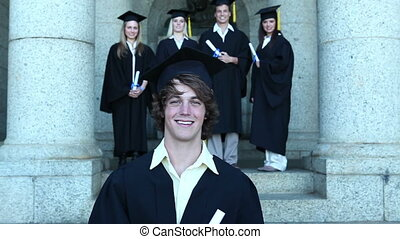 Graduates smiling as they pose - Graduates smiling while...