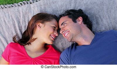 Happy couple lying on a blanket in the countryside