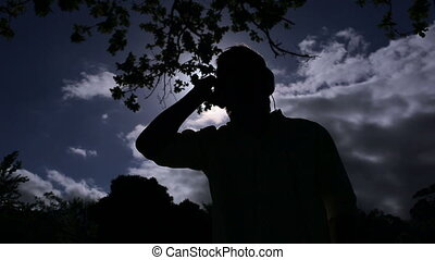 Young man listening to music the in moonlight