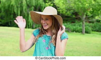 Happy woman holding her straw hat in a park