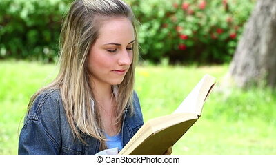 Happy blonde woman reading a novel in the countryside