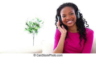 Woman enjoying music with headset on a sofa against white...