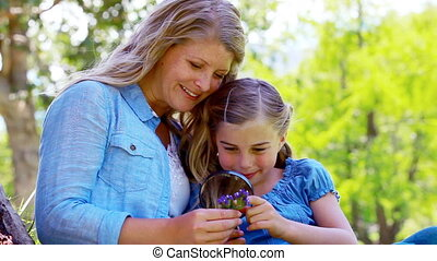 Mother and daughter using a magnifying glass in a park