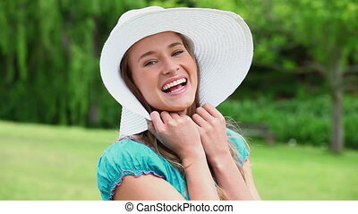 Cheerful young woman holding her hat brim in the countryside