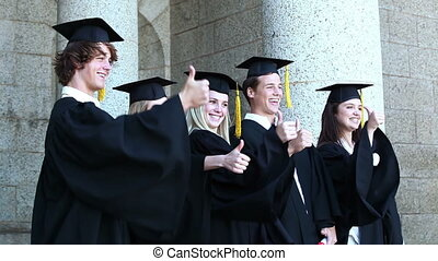 Graduates posing the thumbs-up in front of the university