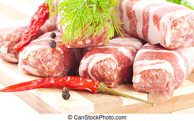 Meat rolls with fennel and red pepper on a bamboo board