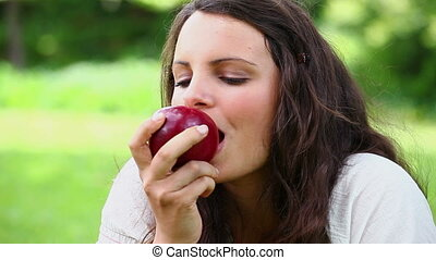 Joyful woman eating a red apple in a park