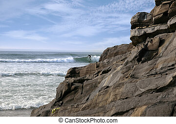 lone surfer near rocks - beautiful clean atlantic ocean with...