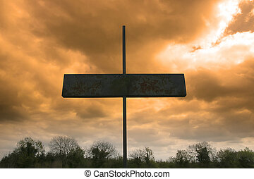metal cross against a red stormy sky