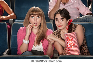 Women With Popcorn Holding Hands