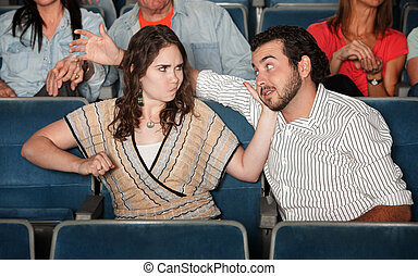 Woman Hits Man in Theater - Irked woman gestures to punch...