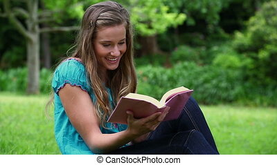 Smiling woman reading a fascinating novel in a park