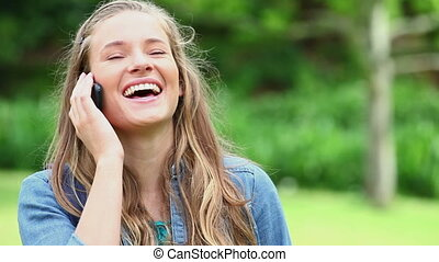 Laughing woman using her cellphone in a park