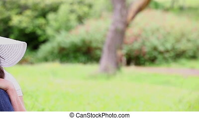 Peaceful woman sitting on the grass