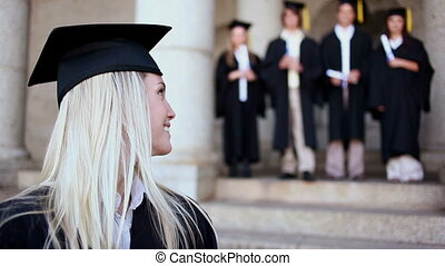 Happy friends standing behind a blonde student in front of...