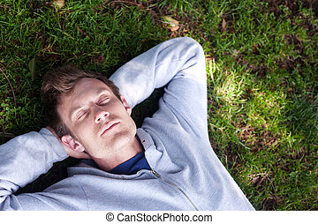 young man sleeping in the grass - handsome young man...